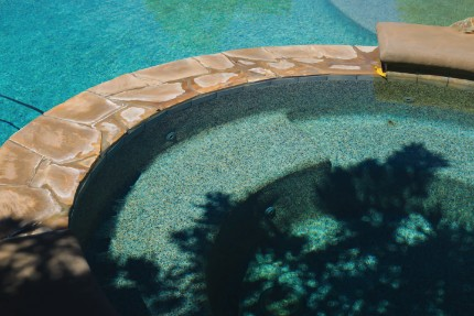 a picture of a spa next to a clean swimming pool. This pool company cleans spas and pools