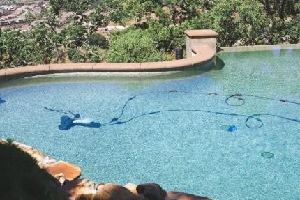 picture of a clean blue pool that was previously green and a pool vacuum cleaning the in ground swimming pool